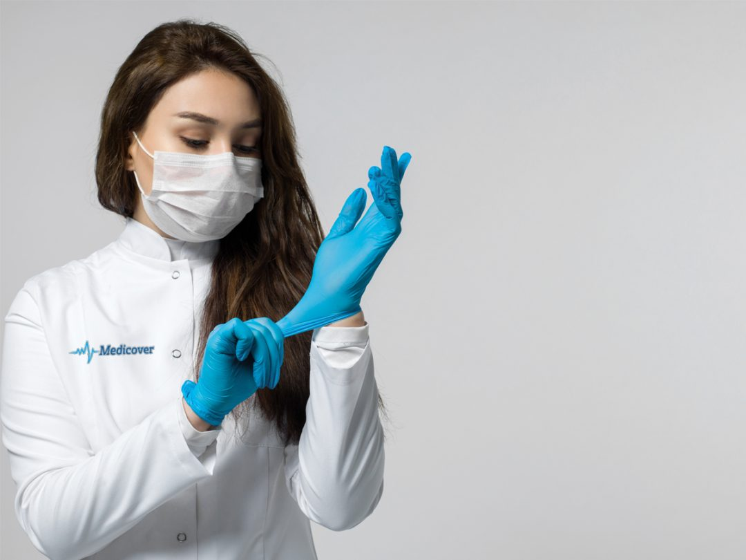 medical worker wearing blue gloves due to covid pandemic in white medical uniform and white protective sterile mask on grey background